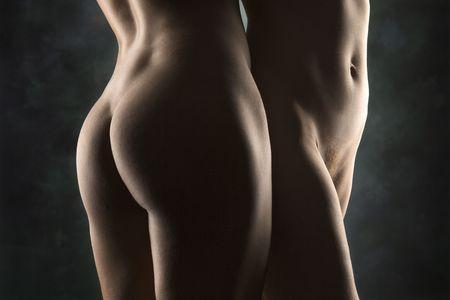 pareja desnuda: Caderas y nalgas desnudas de las mujeres hispanas y de raza cauc�sica de pie juntos.
