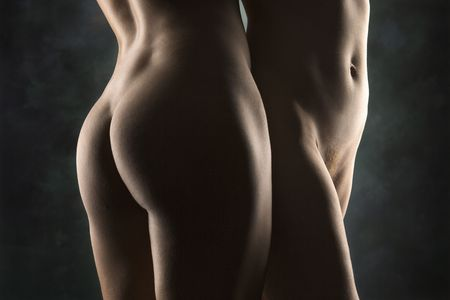 nude butt: Hips and buttocks of nude Hispanic and Caucasian women standing together.