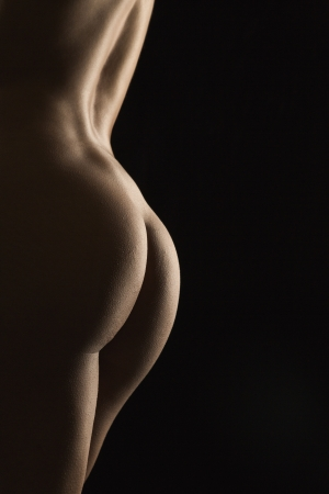 Side view of nude Hispanic mid adult female back and buttocks. photo