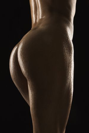 naked women body: Back view of thighs and buttocks of nude Hispanic mid adult woman glistening with body oil.