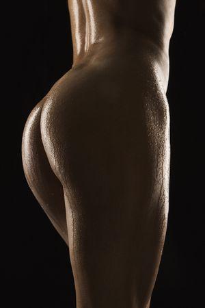 wet nude: Vista posterior de los muslos y las nalgas desnudas de mujer adulta hispana de mediados brillante cuerpo con aceite.