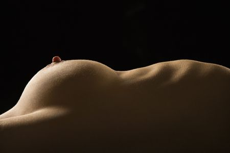 Side view of torso of nude Caucasian woman lying on back.