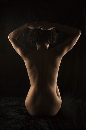 half nude: Back view of nude Hispanic mid adult woman sitting with hands on head. Stock Photo