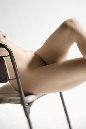 partially nude: Partially nude woman with hands crossed sitting in chair. Stock Photo