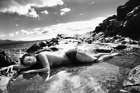 partially nude: Nude Caucasian mid adult woman lying in tidal pool at Maui coast with eyes closed and head on arm. Stock Photo