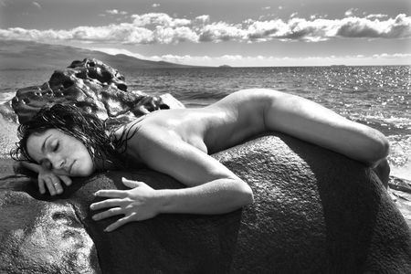 Nude Caucasian mid adult woman draped over rock with at Maui coast in background. photo