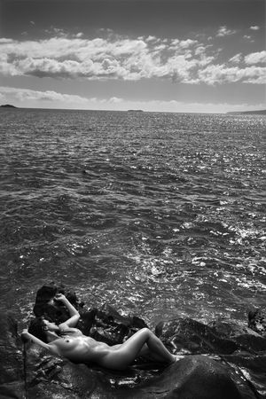 Nude Caucasian mid adult woman nestled in watery alcove at Maui coast. photo