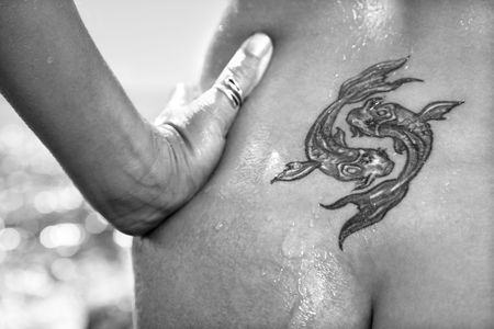 koi: Close up of  wet Caucasian mid adult womans tattoo of koi fish on lower back.