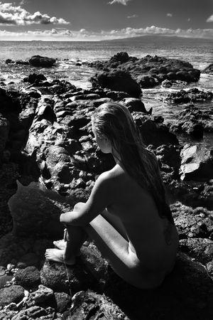 mujer desnuda sentada: Vista posterior del joven filipino mujer desnuda sentada en la playa rocosa.  Foto de archivo