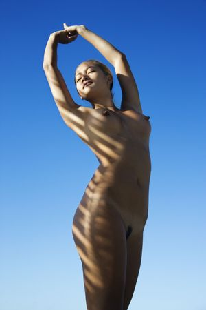 Filipino young nude woman with arms stretched overhead standing with sun streaks over body. Stock Photo