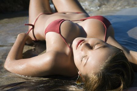 Sexy young adult Asian Filipino female in bikini lying on beach Woman lying on beach in Maui Hawaii. Stock Photo - 2189418