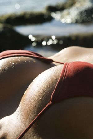 Breast shot of young adult Asian Filipino female lying on beach in bikini. Stock Photo - 2174170