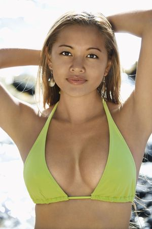 Young adult Asian Filipino female in bikini on beachwith arms raised looking at viewer Close up of buttocks of Asian Filipino young adult female holding jump rope in swimsuit on beach in Maui Hawaii. photo