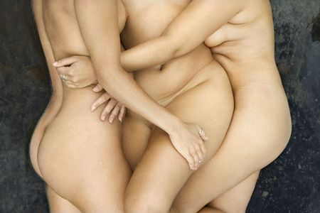 nude outdoors: Three nude Caucasian mid-adult women lying side by side embraciing each other.