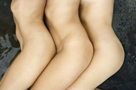 nude outdoors: Three nude Caucasian mid-adult women lying side by side.