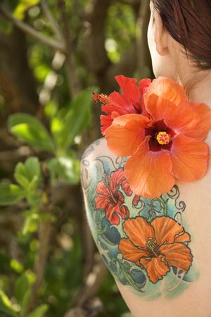 Back view of tattooed Caucasian woman with Hibiscus flower over her shoulder in Maui, Hawaii, USA. Stock Photo - 2174158