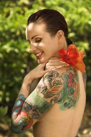 Attractive smiling Caucasian tattooed woman with Hibiscus flower over her shoulder in Maui, Hawaii, USA. Stock Photo - 2189513