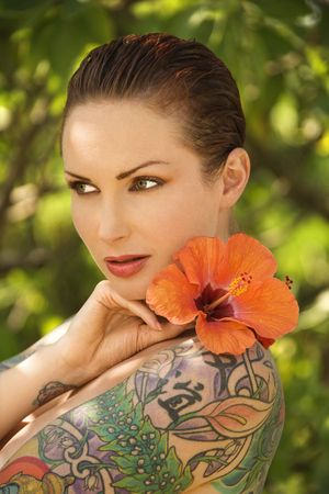 Attractive Caucasian tattooed woman with Hibiscus flower over her shoulder in Maui, Hawaii, USA. Stock Photo - 2189495