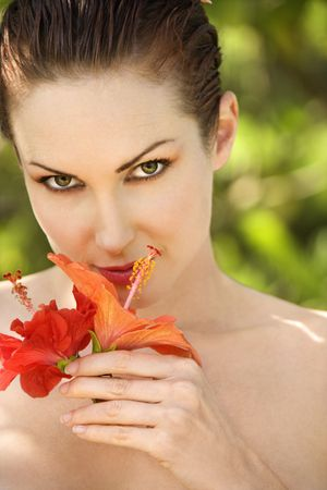 Attractive  smiling Caucasian woman smelling Hibiscus flower in Maui, Hawaii, USA. Stock Photo - 2189409