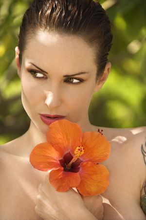 Attractive  Caucasian tattooed woman holding Hibiscus flower in Maui, Hawaii, USA. Stock Photo - 2189376