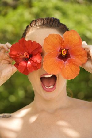 Attractive  Caucasian woman holding Hibiscus flowers over eyes with mouth open in Maui, Hawaii, USA. Stock Photo - 2189339