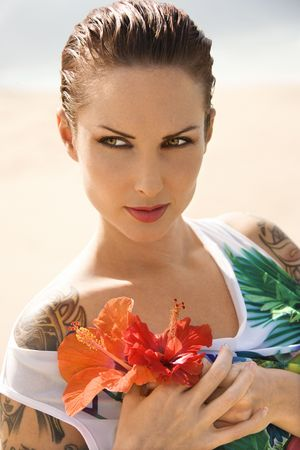 Attractive Caucasian tattooed woman holding Hibiscus flowers in Maui, Hawaii, USA. Stock Photo - 2189403