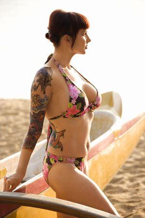 Sexy redheaded Caucasian tattooed woman in bikini beside outrigger canoe on beach in Maui, Hawaii, USA. photo