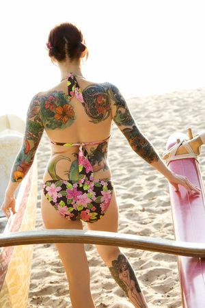 Sexy redheaded Caucasian woman in bikini beside outrigger canoe on beach in Maui, Hawaii, USA. Stock Photo
