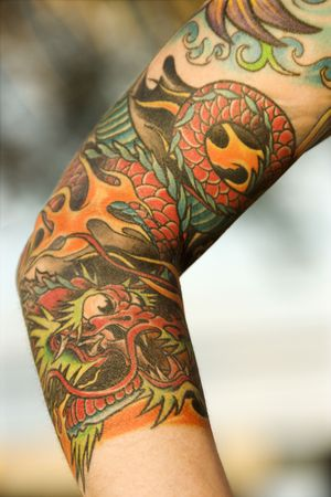 arms body: Close up of dragon tattoo on arm of Caucasian woman. Stock Photo