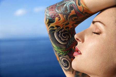 tattoo arm: Close up portrait of tattooed woman with Pacific Ocean in background in Maui, Hawaii, USA.