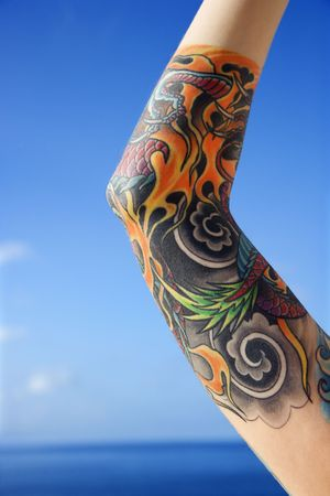 Close up of tattooed womans arm with Pacific Ocean in background in Maui, Hawaii, USA.