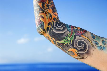 Close up of tattooed woman's arm with Pacific Ocean in background in Maui, Hawaii, USA. Stock Photo - 2174141