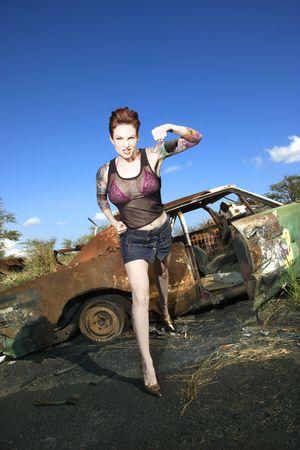 feindschaft: Reizvoll tattooed die kaukasische Frau, die mit dem defiant Blick steht, der vor altem verrostetem Auto im junkyard locht. Lizenzfreie Bilder