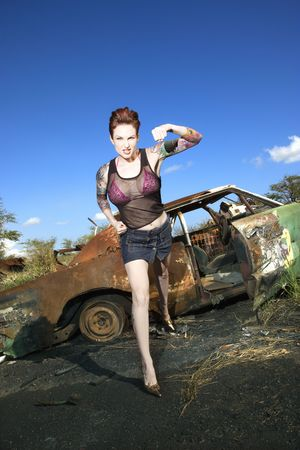 defiant: Sexy tattooed Caucasian woman standing with defiant look punching in front of old rusted car in junkyard. Stock Photo