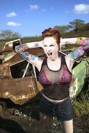 junkyard: Sexy tatuada mujer de raza cauc�sica gritos y la celebraci�n de sus manos sobre sus orejas en chatarrer�a.  Foto de archivo