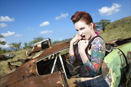 mean: Angry tattooed Caucasian woman with fists clenched ready to fight in junkyard.