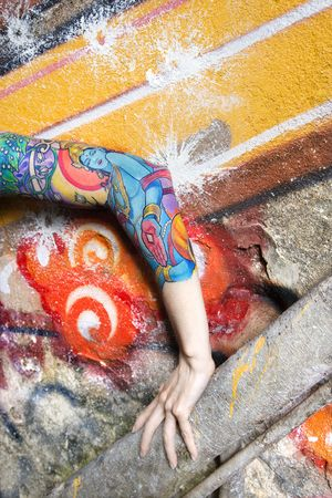 Tattooed Caucasian woman's arm against graffiti covered wall. Stock Photo - 2168723