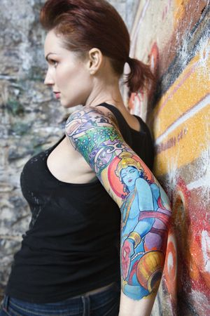Sexy tattooed Caucasian woman leaning on wall covered in graffiti. Stock Photo