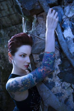 Blue-toned portrait of fearful looking tattooed Caucasian woman next to concrete wall in Maui, Hawaii, USA. Stock Photo - 2189584
