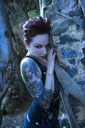 the sleeve: Blue-toned portrait of fearful looking tattooed Caucasian woman next to concrete wall in Maui, Hawaii, USA.