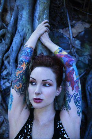banyan: el retrato Azul-entonado de tattooed a mujer cauc�sica con el �rbol del banyan en Maui, Hawaii, los E.E.U.U..