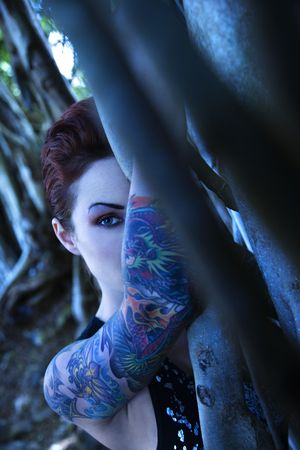 Blue-toned portrait of tattooed Caucasian woman hiding behind Banyan tree in Maui, Hawaii, USA. Stock Photo