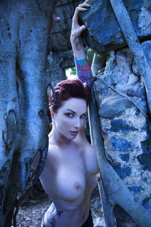 half nude: Blue-toned portrait of sexy nude Caucasian tattooed woman next to Banyan trees in Maui, Hawaii, USA.
