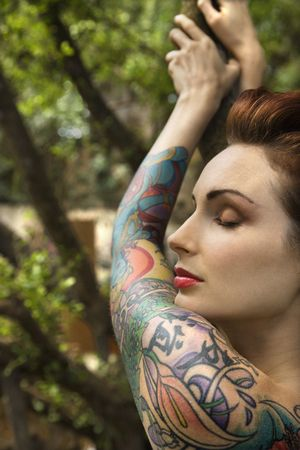tattooed Caucasian woman in forest leaning on tree in Maui, Hawaii, USA.