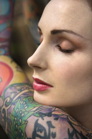 Close-up portrait of attractive woman's face and tattooed arm. Stock Photo - 2189843