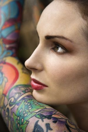 Close-up of attractive Caucasian womans face and tattooed arm.