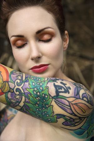 Close-up of attractive Caucasian nude womans face and tattooed arm.