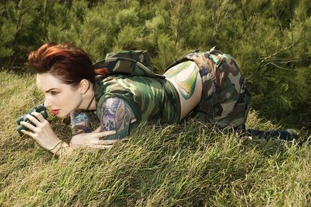 military watch: Attractive tattooed Caucasianwoman in camouflage lying on grass looking through binoculars in Maui, Hawaii, USA.