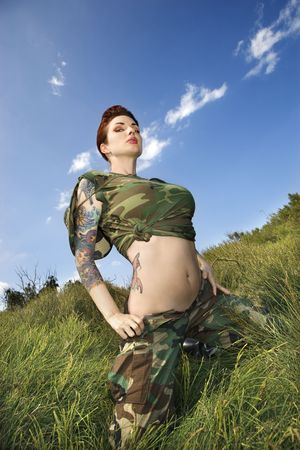 Attractive tattooed Caucasian woman in camouflage crouching in grass in Maui, Hawaii, USA.