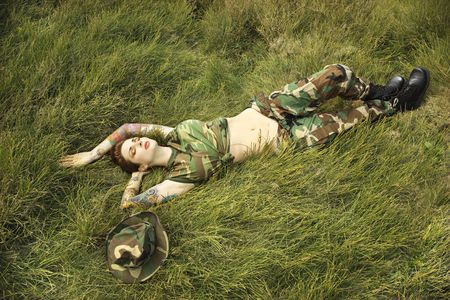 camouflage woman: Attractive tattooed Caucasian woman in camouflage lying on grass in Maui, Hawaii, USA.